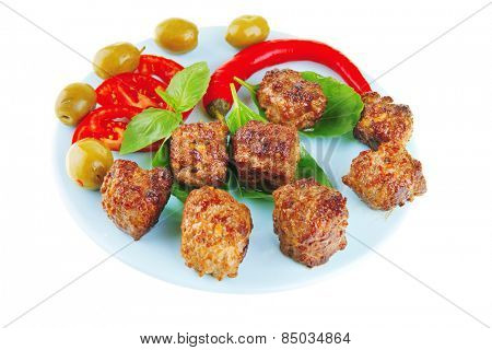 roast meat balls on basil over blue dish