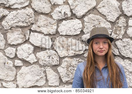 Adolescent girl in a hat and denim jacket against a white stone walls.