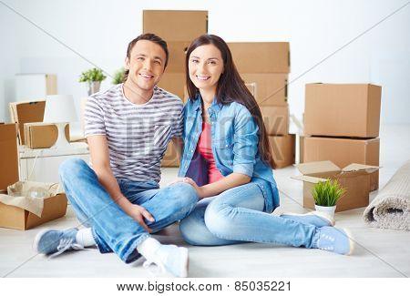 Happy couple sitting among unpacked boxes