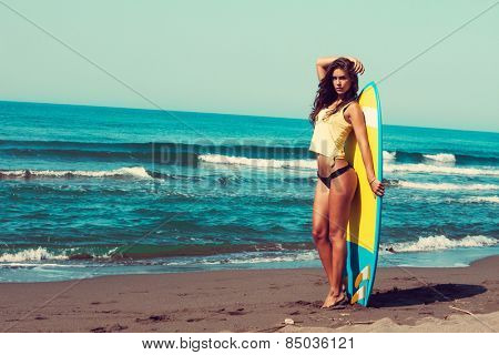 young woman stand on beach hold surfboard , sunny summer day, full body shot