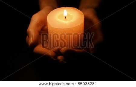 Candle in female hands on black background