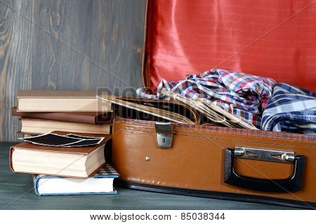 Vintage suitcase open with clothes and books on wooden background