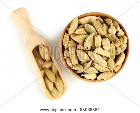 Cardamom in wooden bowl, isolated on white