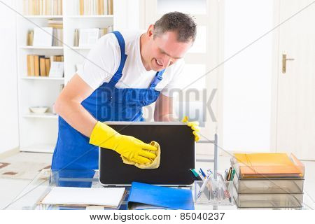Smiling man cleaner wiping laptop at the office