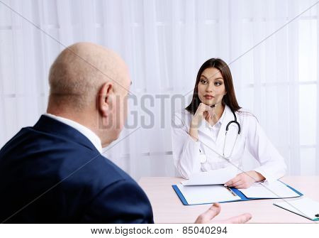 Young female doctor receiving patient in her office on white curtain background