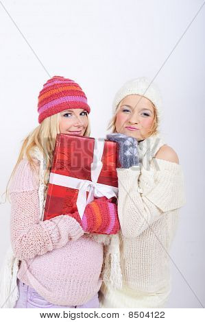 two beautiful winter girl friends with christmas presents
