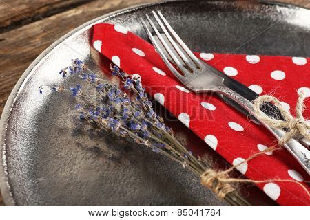 Silverware tied with rope on metal tray with colorful napkin and dried flower on wooden planks background