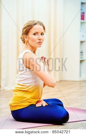 Beautiful athletic girl doing yoga exercises indoor. Lotus pose. Meditation.