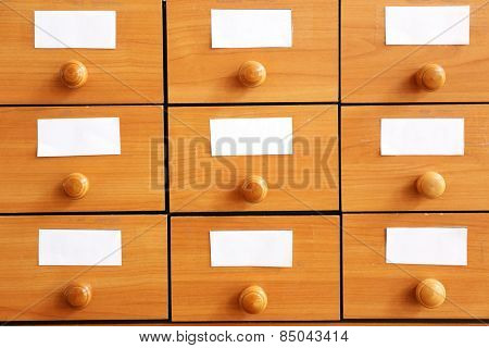 Wooden drawers with catalog cards in library, closeup