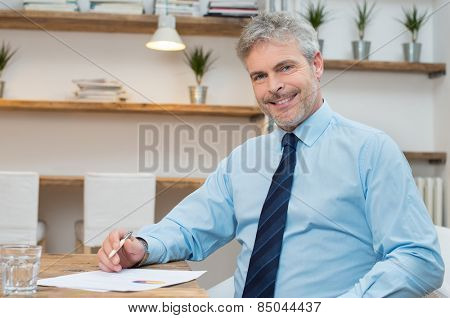 Portrait of mature businessman sitting at desk with stockmarket document