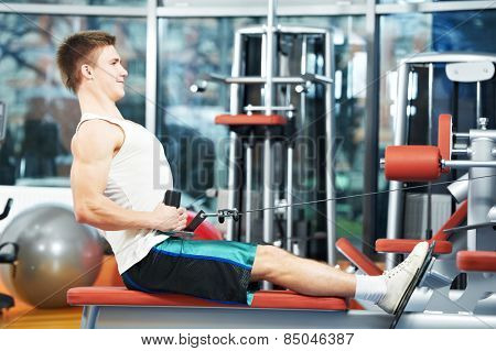 man with training equipment at fitness club gym doing exercises for back muscles