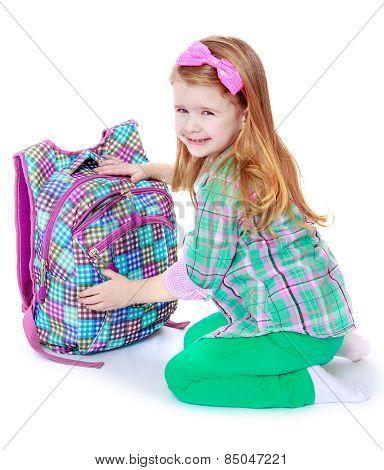 charming schoolgirl on her knees opens his satchel