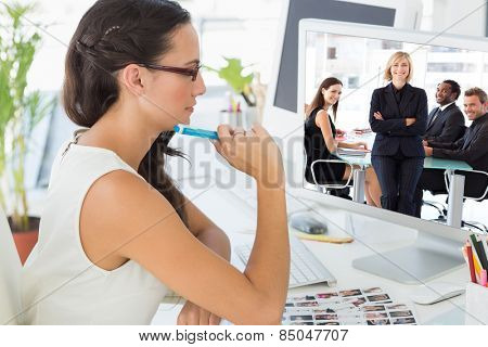 Business team smiling at the camera in a meeting against focused young editor working at her desk