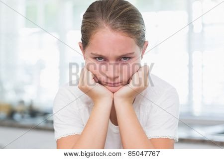 Upset little girl looking at camera at home in the kitchen