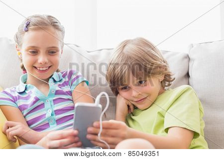 Siblings listening music through mobile phone on sofa at home