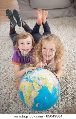 High angle portrait of brother and sister with globe lying on rug at home
