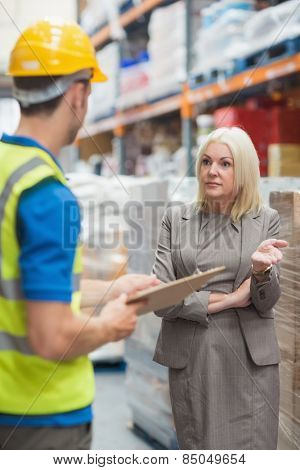 Worker with clipboard speaking with his manager in warehouse