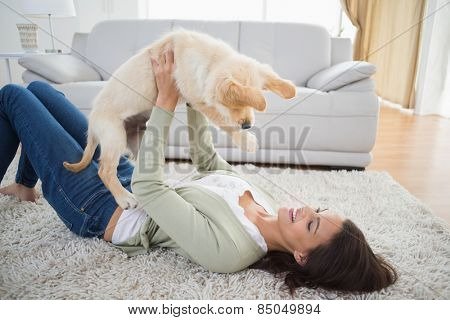 Happy young woman lifting puppy while lying on rug at home