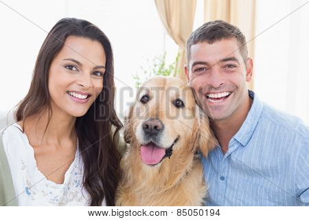 Portrait of happy couple with dog at home