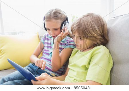 Siblings using digital tablet while listening music on sofa at home