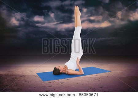 Fit woman stretching body in fitness studio against dark cloudy sky