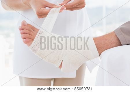 Doctor bandaging her patient leg in medical office