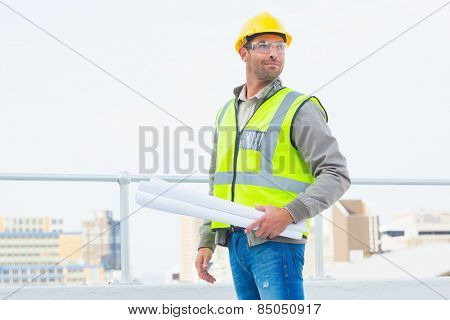 Confident architect in protective clothing holding rolled up blueprints outdoors