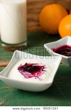 White Yogurt In A Bowl With Fruit Placed On Green Table