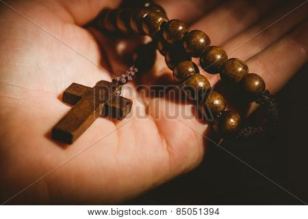 Hand holding wooden rosary beads in close up