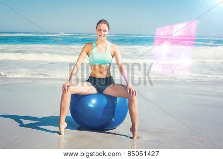 Fit woman sitting on exercise ball at the beach against fitness interface