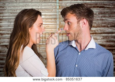 Casual young couple in an argument against wooden planks