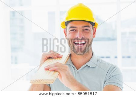 Portrait of cheerful male carpenter wearing hardhat while carrying planks