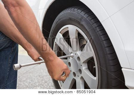 Man fixing tire of his car