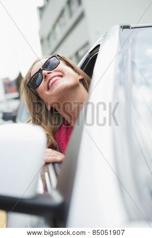 Happy woman in the drivers seat in her car