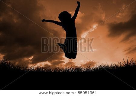 Silhouette of little girl jumping against cloudy sky
