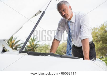 Upset man checking his car engine after breaking down on the road