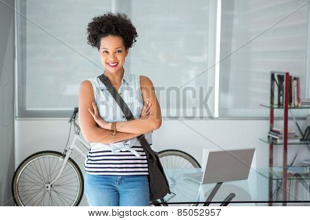 Portrait of casual young woman standing with arms crossed