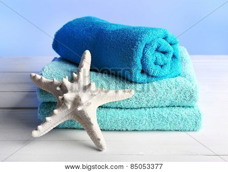 Terry towels with starfish on wooden table and light colorful background
