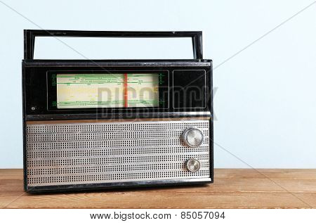 Retro radio on wooden table on light colorful background