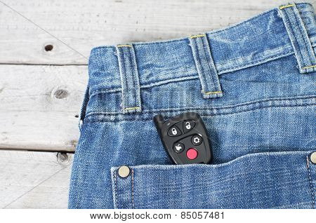 Car Remote Starter In Blue Jeans Back Pocket Against Wooden Background