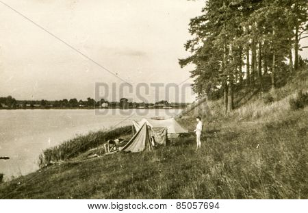 Vintage photo of young man camping during a canoe trip (1960's)