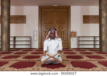 Black Businessman In Dishdasha Is Reading The Quran