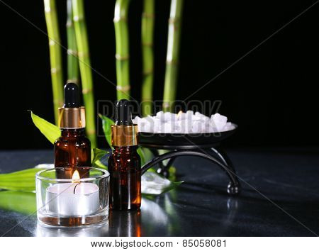 Beautiful composition with aromatic oils and candle on table on dark background