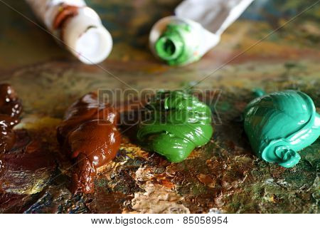 Acrylic paint with paint tubes on wooden palette