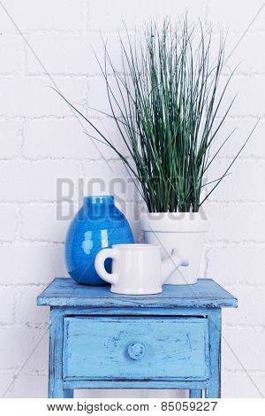 Interior design with plant, decorative vase and watering pot on tabletop on white brick wall background