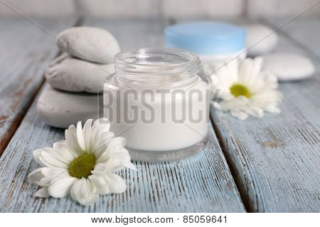 Cosmetic cream with flowers and spa stones on wooden background