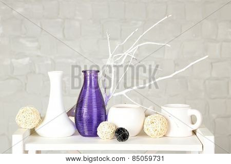 Interior with decorative vases and branch twig on table top and white brick wall background