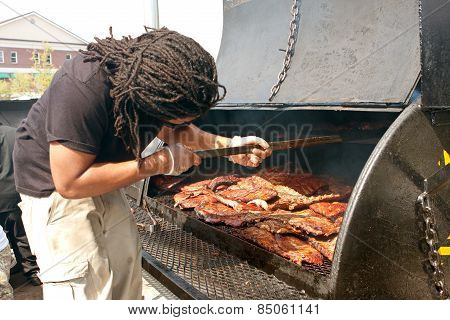 Man Cooks Slabs Of Ribs On Grill At Barbeque Festival