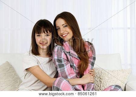 Two girls in pajamas sitting on sofa