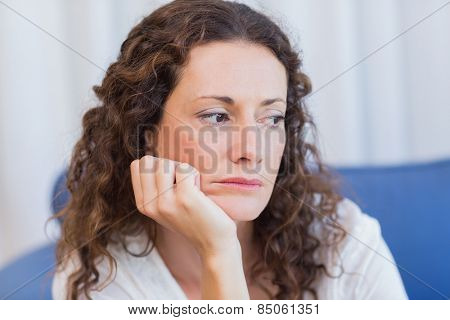 Worried woman sitting on the couch in the living room